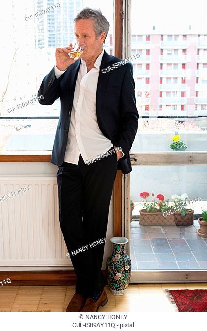 Man in smart clothes drinking beside window