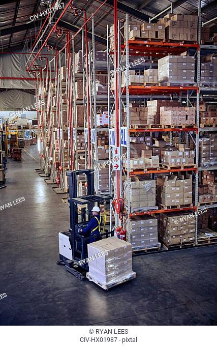Worker operating forklift moving cardboard boxes near distribution warehouse shelves