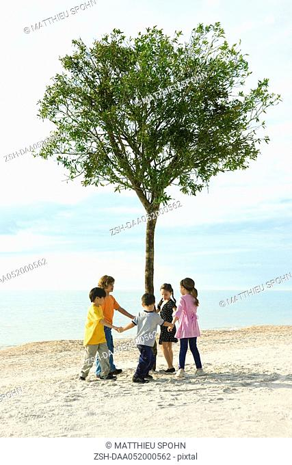 Group of children holding hands in circle around solitary tree on beach