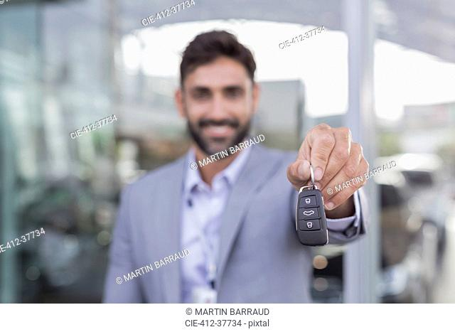 Portrait smiling, confident car salesman holding, showing new car keys