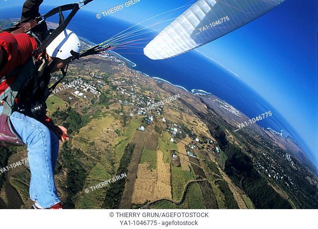 Aerial view of a tandem paraglider pilots over sugar cane fields near Saint Leu. Reunion island (archipelago of Mascarenhas), French department island