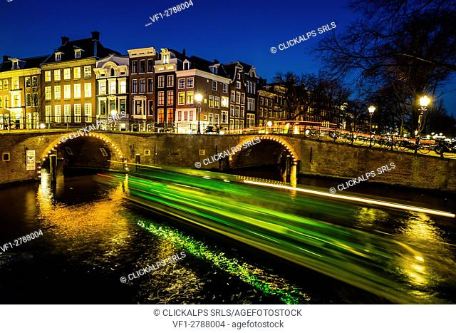 Amsterdam, Netherlands, Europe. Canal and light trails of a vessel