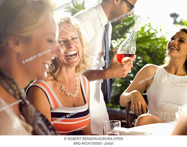 A waiter serves wine to three beautify ladies sit in the open in San Diego