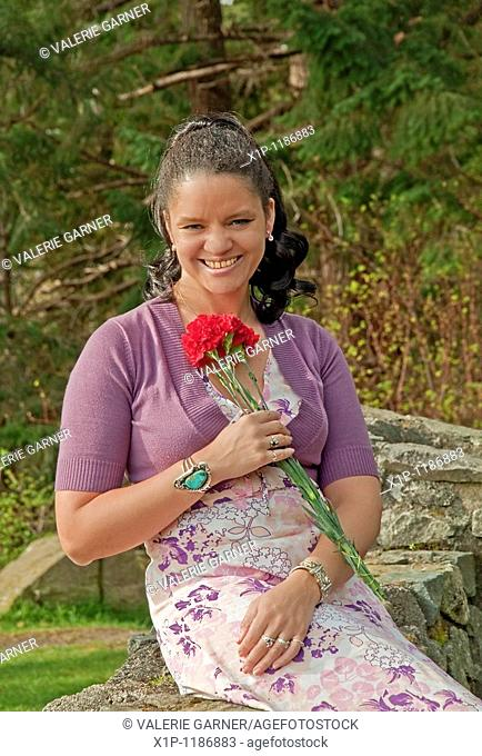 This pretty multi racial woman in her thirties is smiling and confident as she's outdoors in this vertical portrait She's wearing a pastel colored floral dress...
