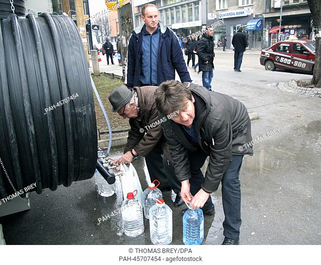 Residents fill bottles with drinking water from a water barrel in Uzice, Serbia, 17 January 2014. About 6,000 people are living without tab water for four weeks...