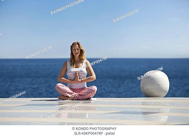 Woman meditating on tiled surface