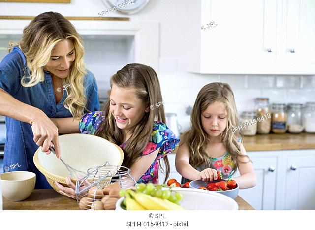 MODEL RELEASED. Mother and two daughters cooking in the kitchen