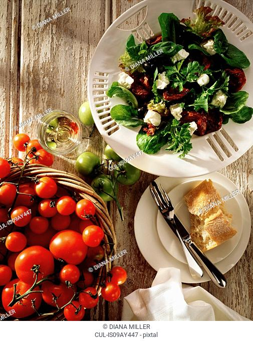 Mediterranean salad, feta cheese, black olives, sun dried tomatoes, salad leaves with fresh tomatoes in basket, overhead view