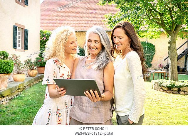 Three happy women of different age using tablet in garden