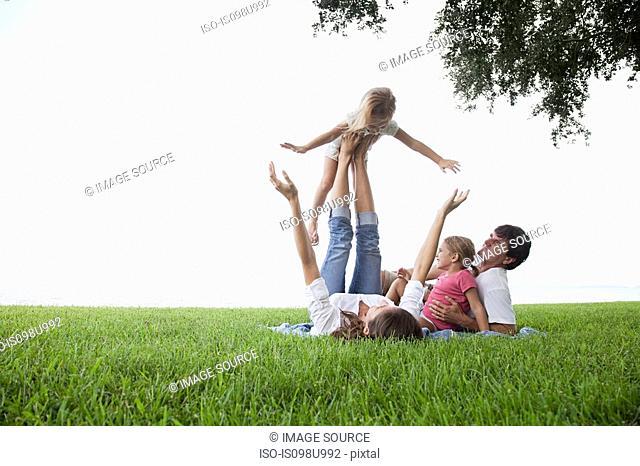 Girl balancing on feet of mother