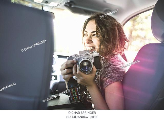 Young woman photographing from front seat of car