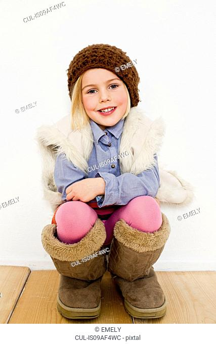 Studio portrait of young girl in oversize boots