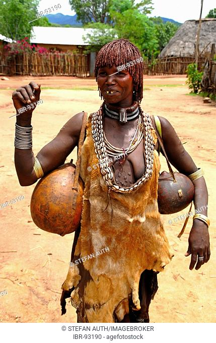 Woman of the Hamar people wears a leather cloth and typical clay hairdo a metal and kauri mussel chain and kalabasses at the market of Dimeka Ethiopia