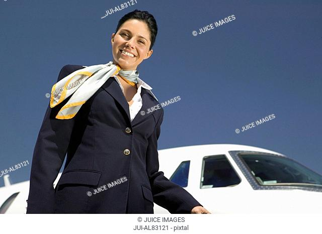 Female flight attendant smiling in front of airplane