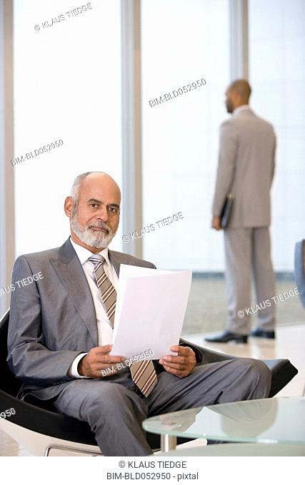 Senior African businessman holding paperwork