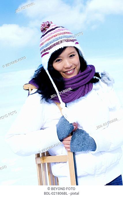 portrait of young asian woman in winter carrying sledge