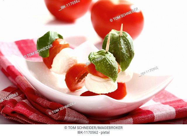 Tomato-mozarella sticks with basil