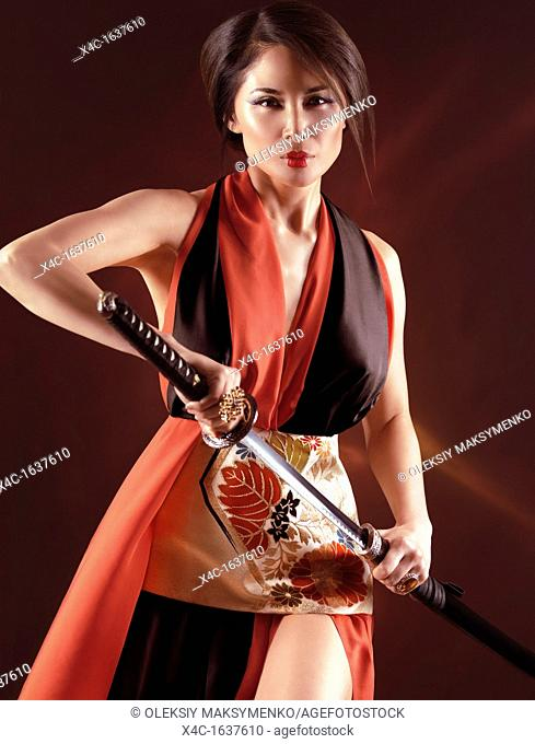 Beautiful asian woman in red and black kimono unsheathing a sword