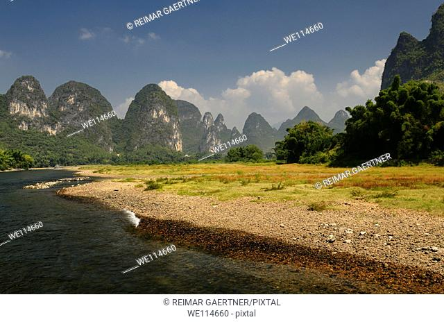 Pebble shore of the Lijiang River China with pointed Karst cones and peaks