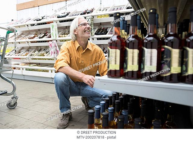 Customer looking wine bottles in supermarket and smiling , Augsburg, Bavaria, Germany