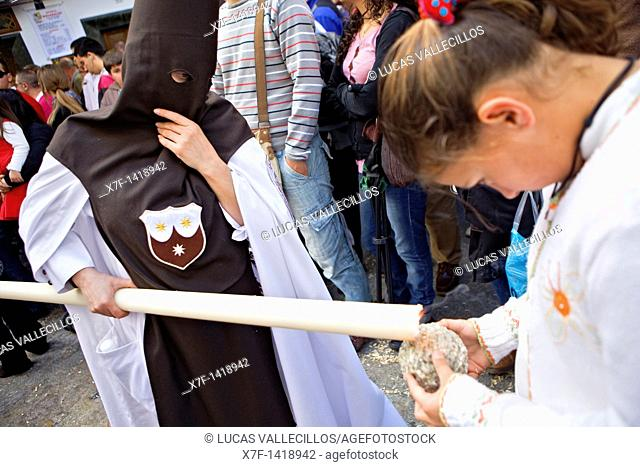 Penitent and girl Girl making a ball of wax Holy Week procession `El Carmen Doloroso' Holy Wednesday  Seville  Spain