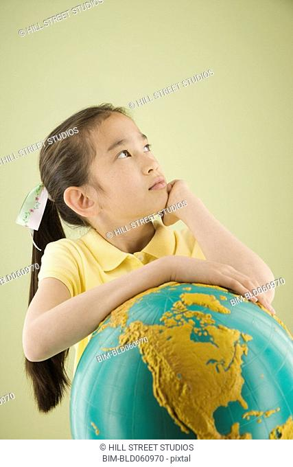 Asian girl leaning on globe