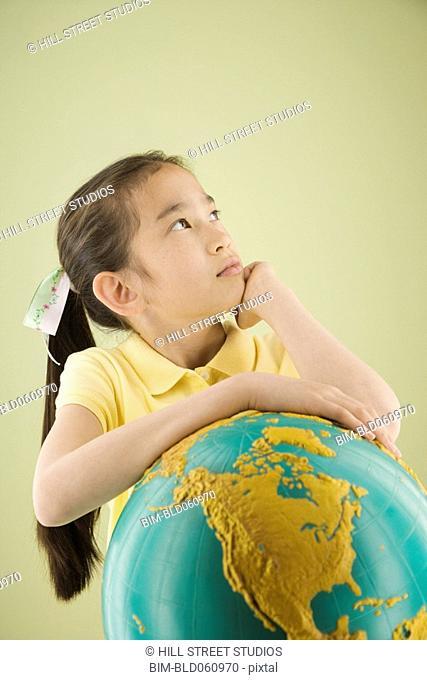 Asian girl leaning on globe