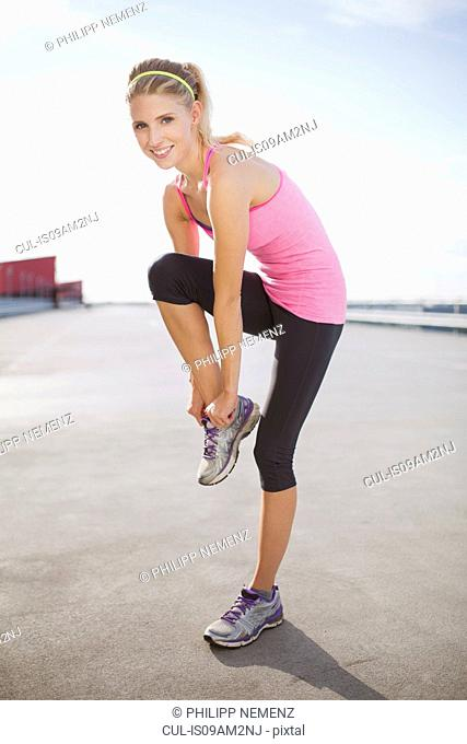 Young woman putting on trainers