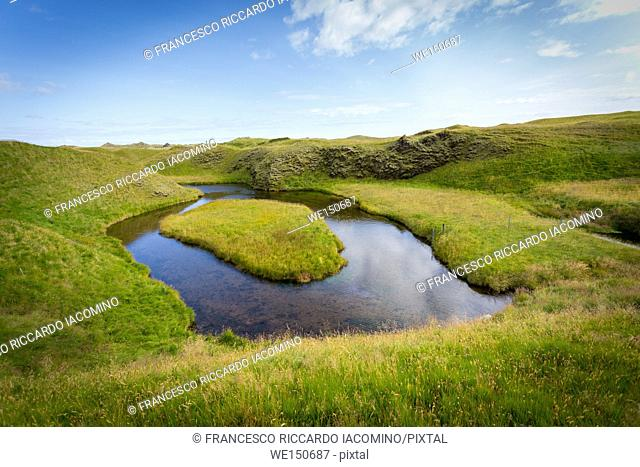 Iceland, green landscape and river meander with grass island
