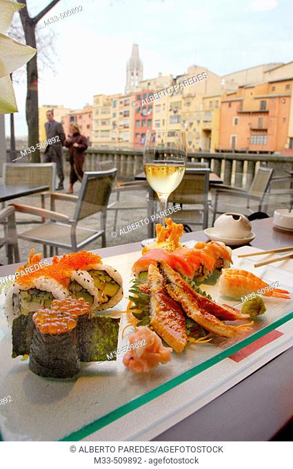 Sushi.'Riba-Sushi Bar'. Houses by Onyar river and Sant Feliu Church in background. Girona, Catalonia , Spain