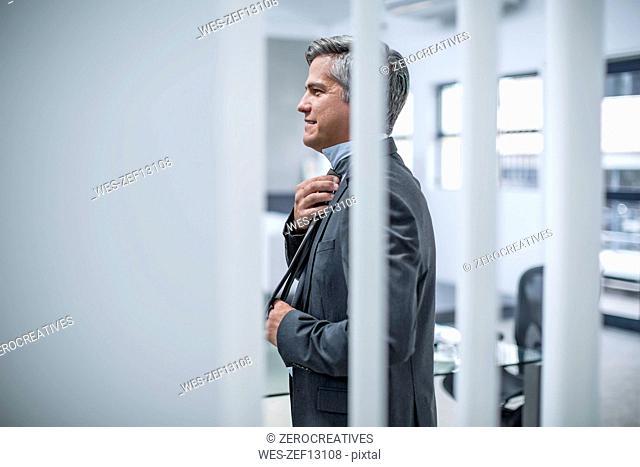 Businessman adjusiting tie in office
