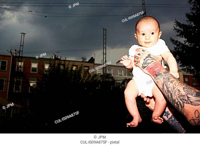 Father with tattooed arms holding baby son