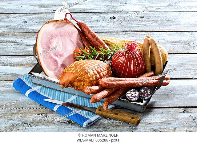 Studio, variety of ham, sausages, tomatoes, rosemary and bread, served on tray