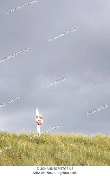 Lifebuoy in front of storm clouds on the beach of Vester Sømarken, Europe, Denmark, Bornholm