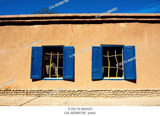 Detail of building exterior with blue window shutters, San Pedro de Atacama, Atacama Desert, Chile