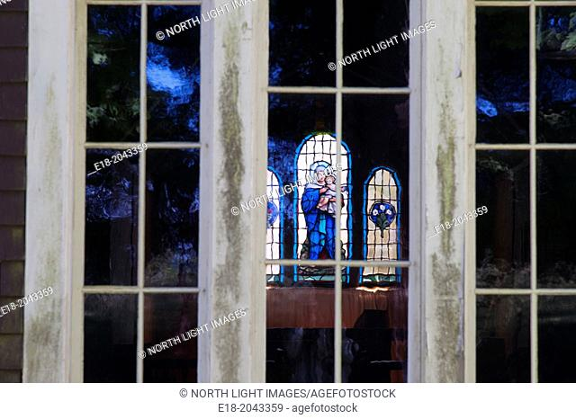 Canada, BC, Saltspring Island, Fulford Harbour. View of stained glass window through regular glass window of church