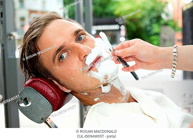 Young man in barbershop, face covered in shaving cream being shaved with straight razor looking away