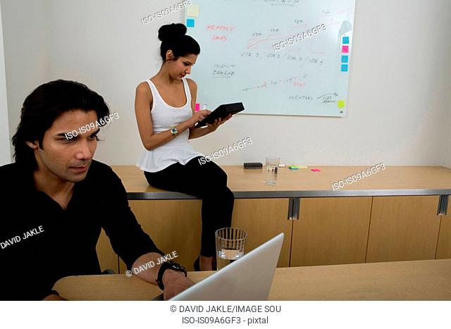Young man using laptop with woman in background