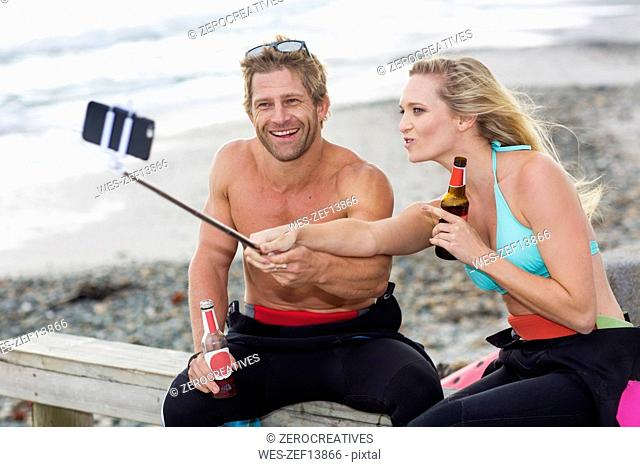 Couple having fun on the beach taking a selfie