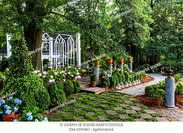 Outdoor living space in a garden setting featuring hydrangeas and boxwoods, pathway and hardscape structure. Georgia USA