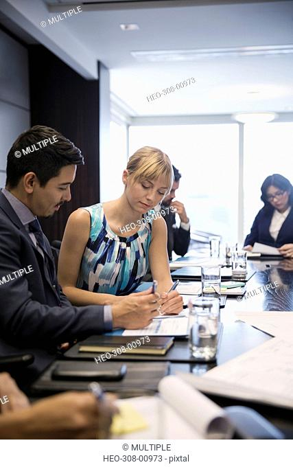 Businessman and businesswoman reviewing paperwork in conference room meeting
