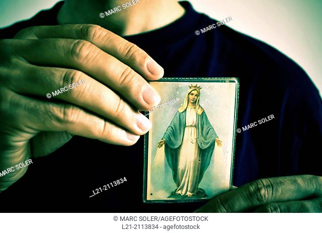 Hands holding picture of Our Lady of the Miraculous Medal