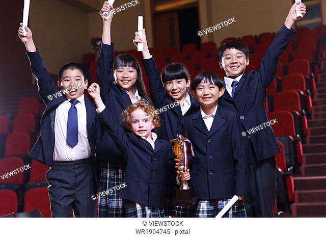 Students hold high the arm to take the prize in the auditorium