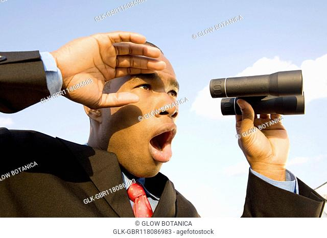 Close-up of a businessman holding binoculars and looking shocked