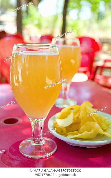 Spanish aperitif: two glasses of clara beer with lemon and chips in a terrace. Spain
