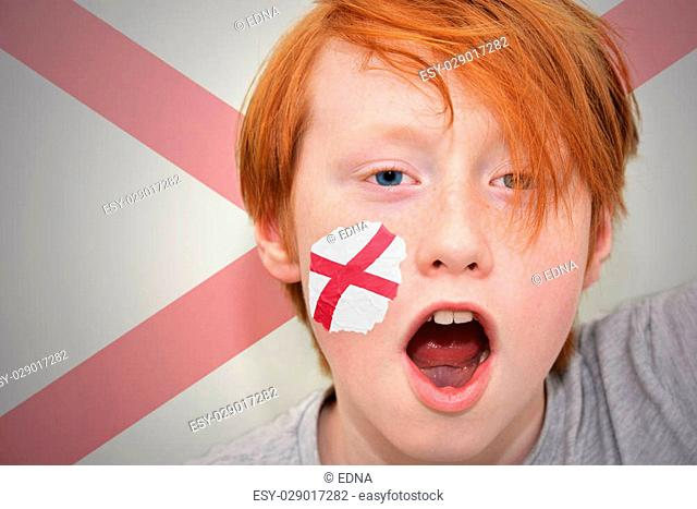 redhead fan boy with alabama state flag painted on his face. on the alabama state flag background
