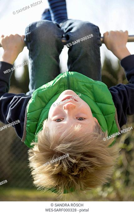Boy exercising on high bar