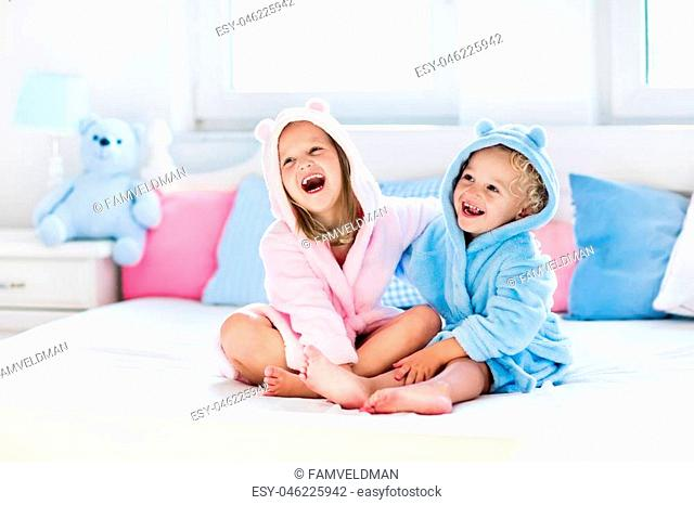 Happy laughing kids, boy and girl in soft bathrobe after bath play on white bed with blue and pink pillows in sunny bedroom