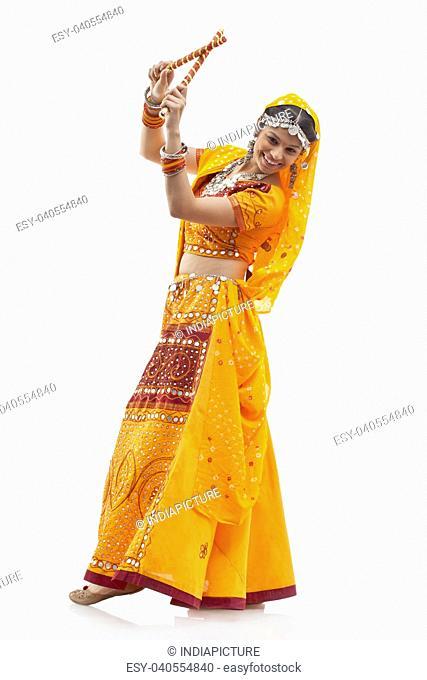 Portrait of happy young woman in chaniya choli performing Dandiya Raas against white background