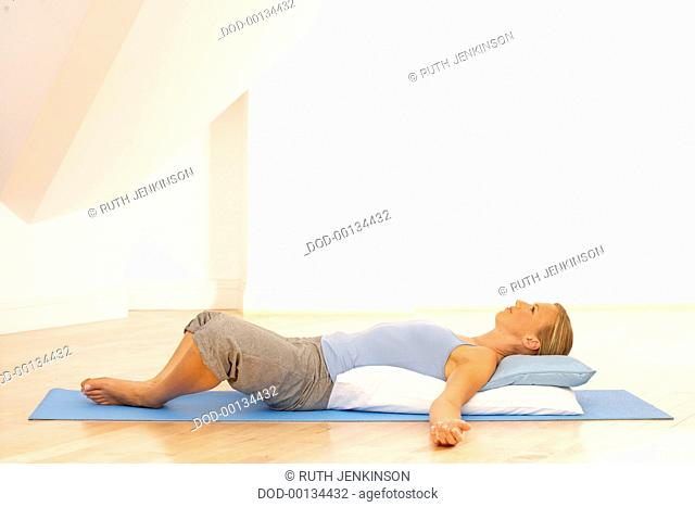 Woman in pale blue vest and grey tracksuit bottoms lying on yoga mat on top of small blue pillow with large white pilow underneath, soles touching, arms spread